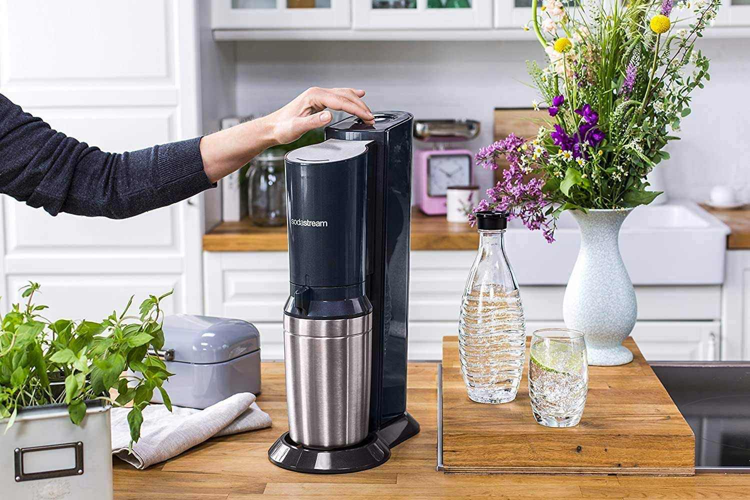 Person using a carbonated water maker