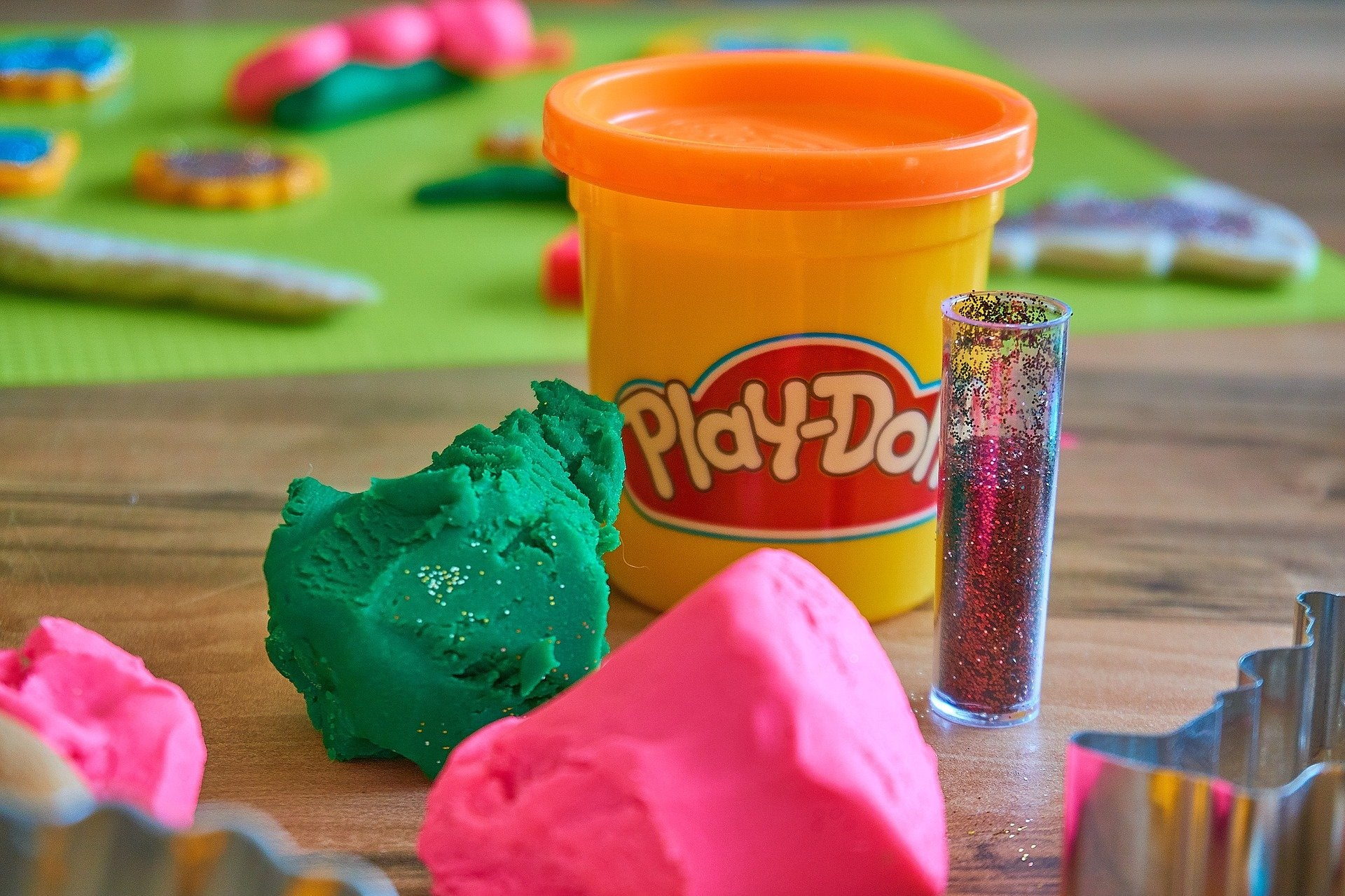 pink and green play doh with a tube of glitter in front or a canister of orange Play-Doh modeling compound