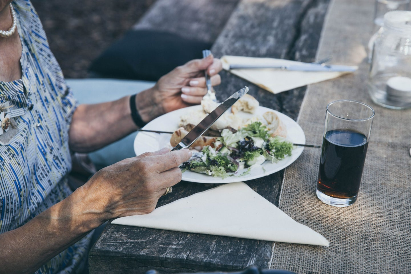 person eating off a white plate at a picnic table with a brown runner and white cloth napkins