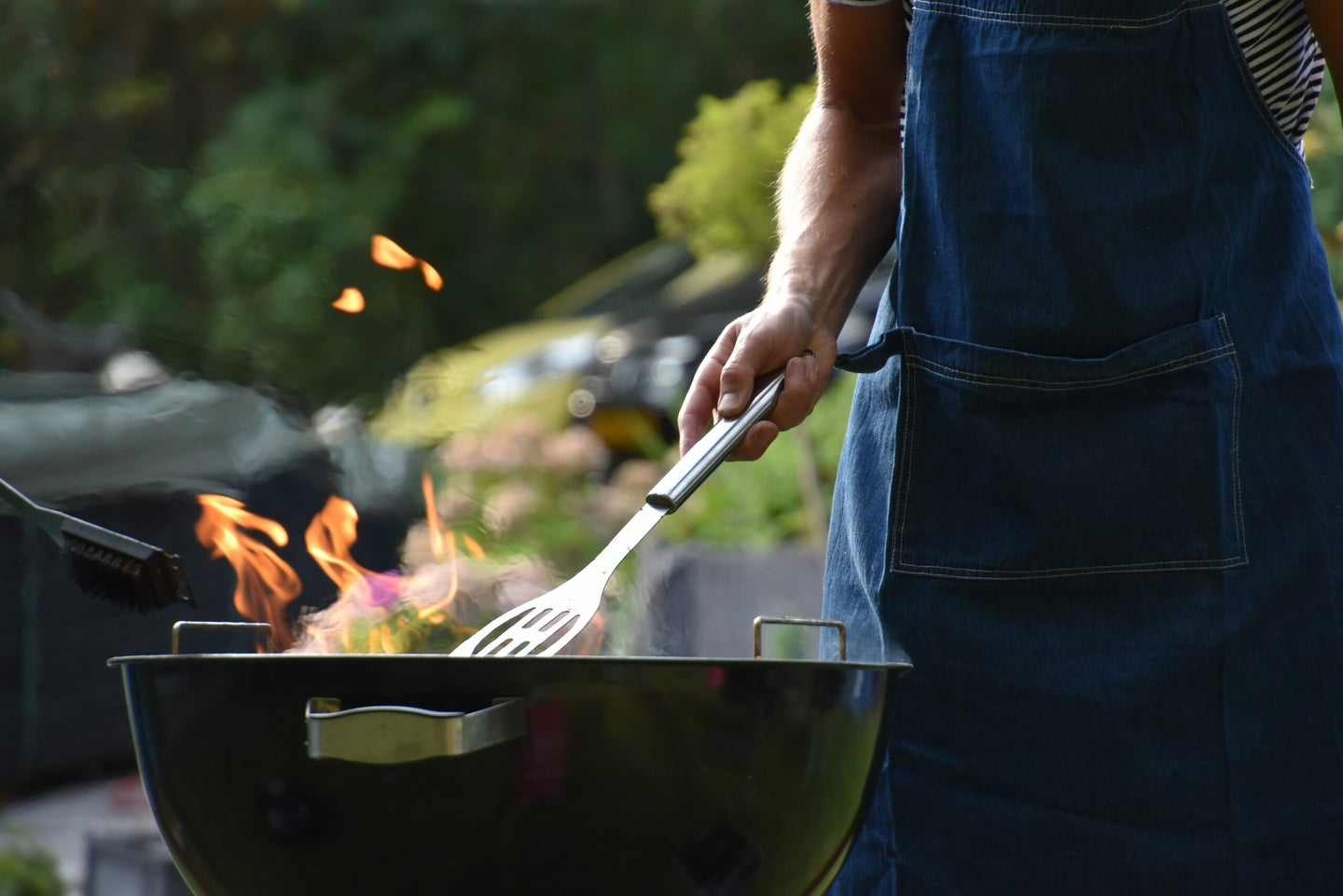 man grilling on an open barbecue