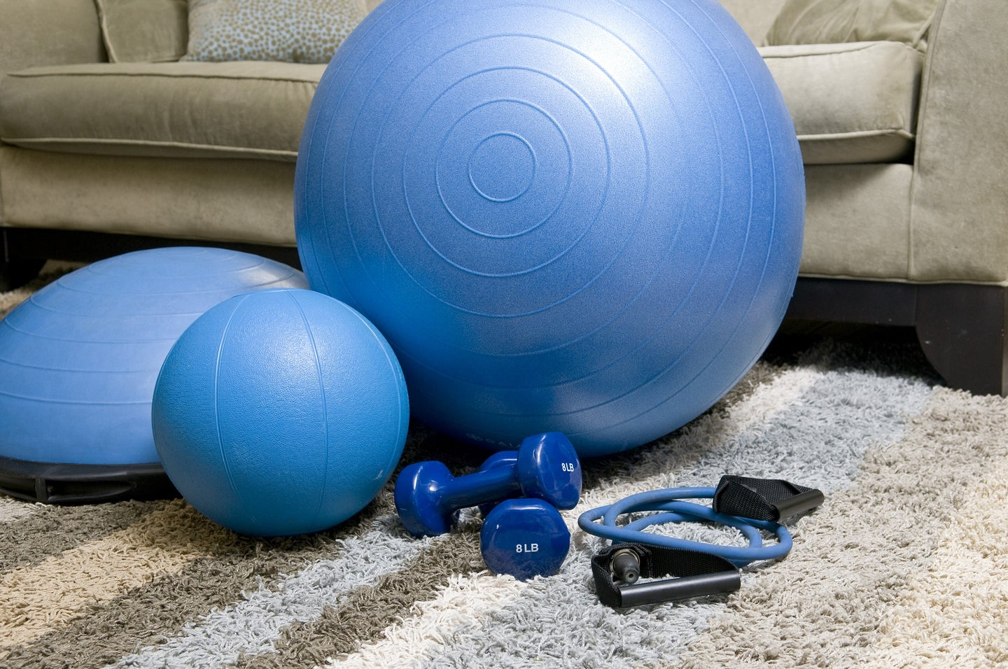 blue hand weights and other exercise equipment on a tan carpet