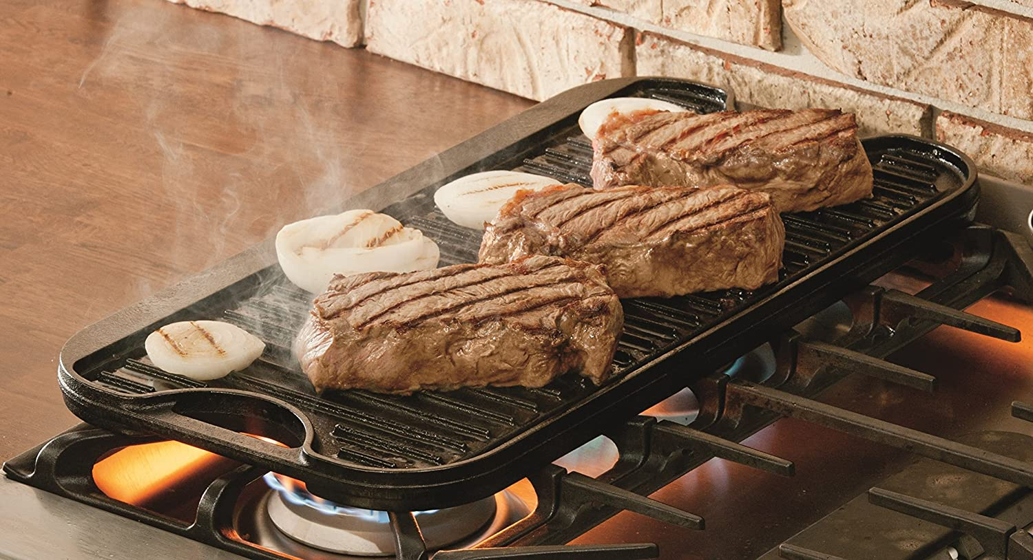 steaks and onions cooking on a reversible griddle atop stove burners