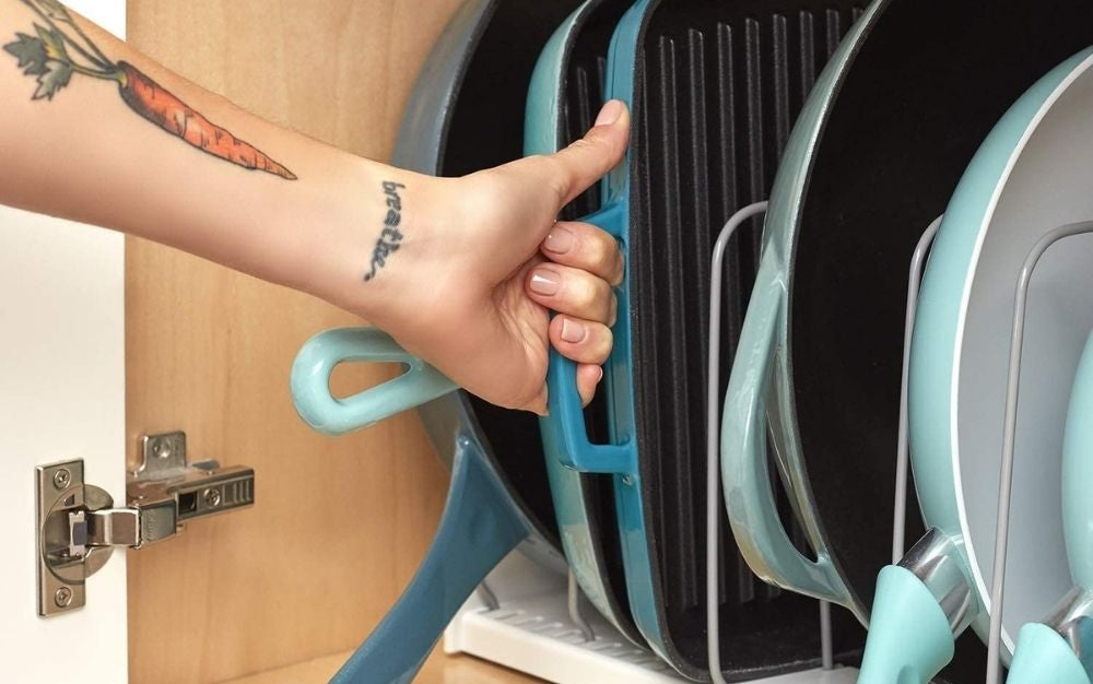 A person reaching out for a lid from the pot lid organizer