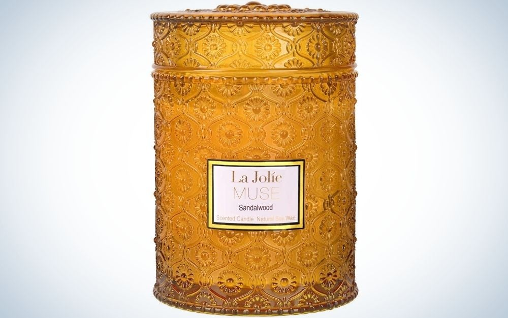 Candle in a golden glass container and white label