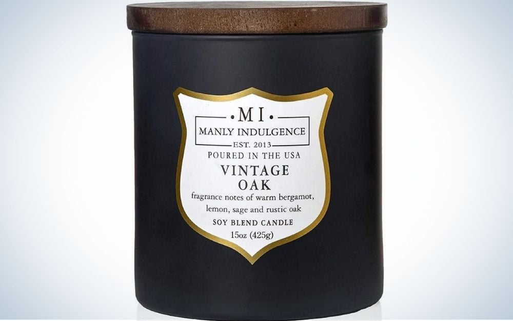 Candle in a black container with wood top and white label