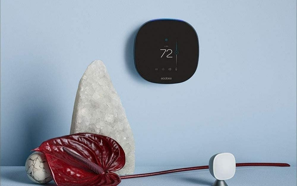 Black thermostat hanging on the white wall
