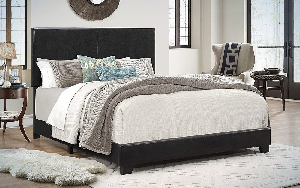 dark upholstered bed frame with a beige bedspread in a room with two rugs