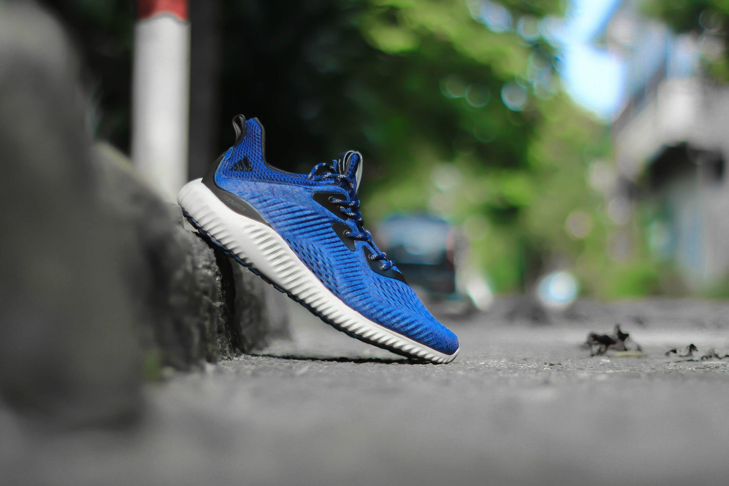 blue sneaker with the heel on the curb and toe on the street
