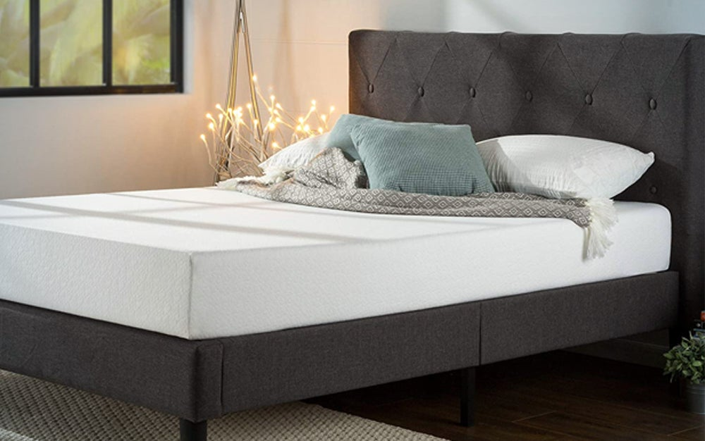 gray upholstered headboard and bed frame in a bedroom with pillows stacked on top