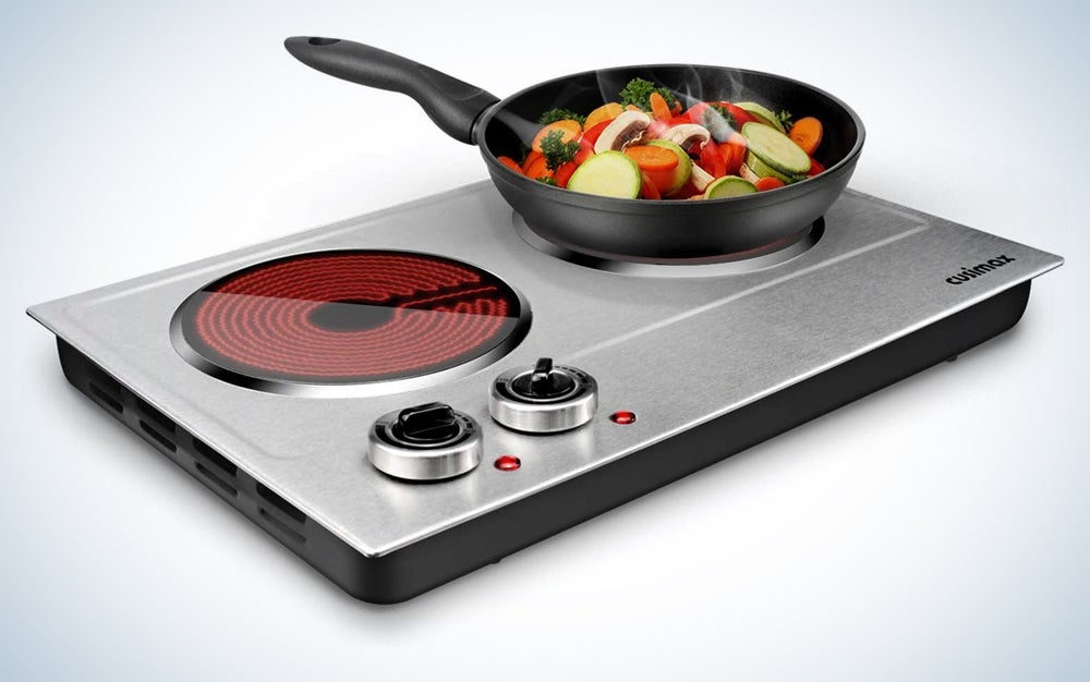 silver hot plate with two knobs, a pan on one burner, and the other burner on
