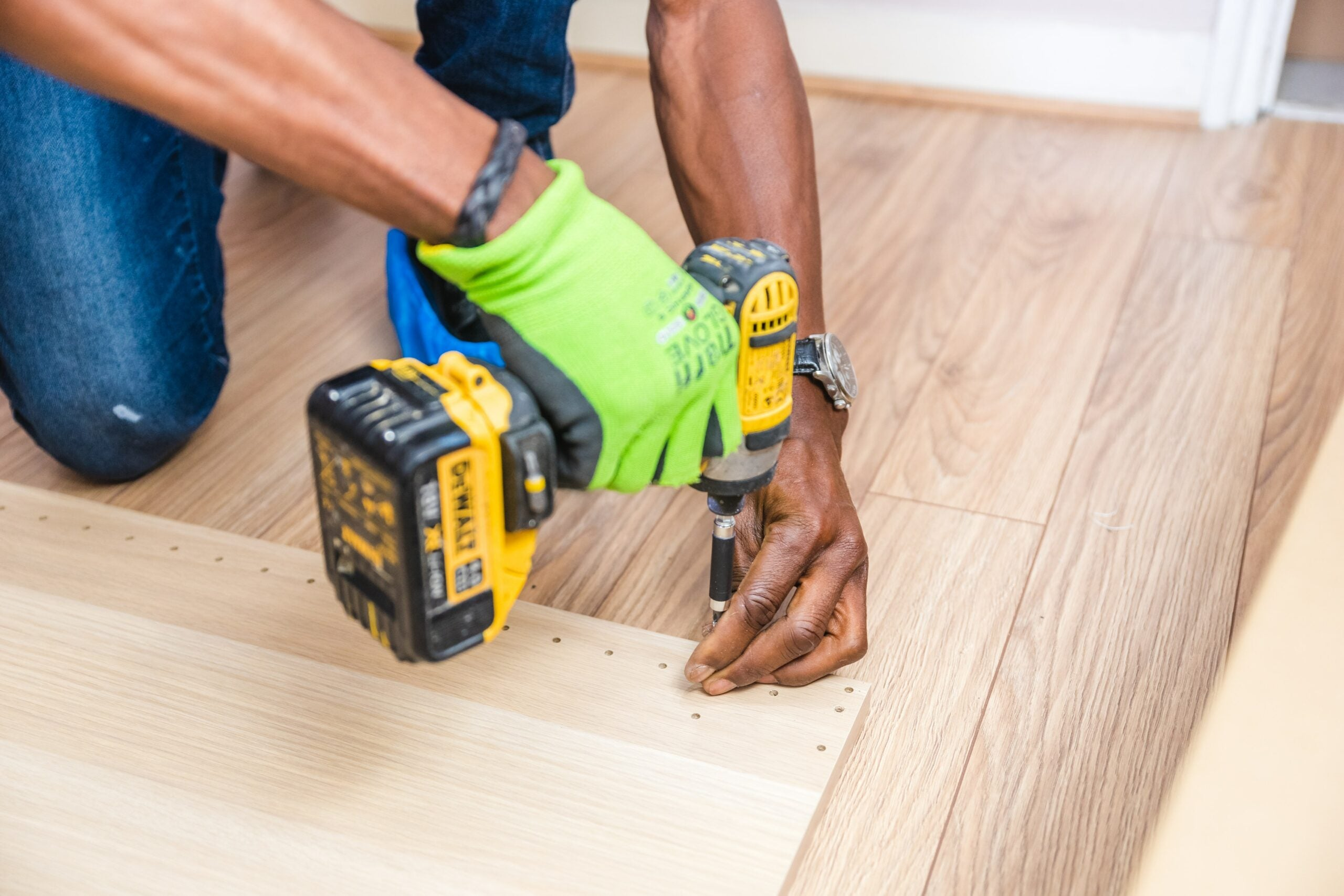 man using a drill to put a screw into a board of wood