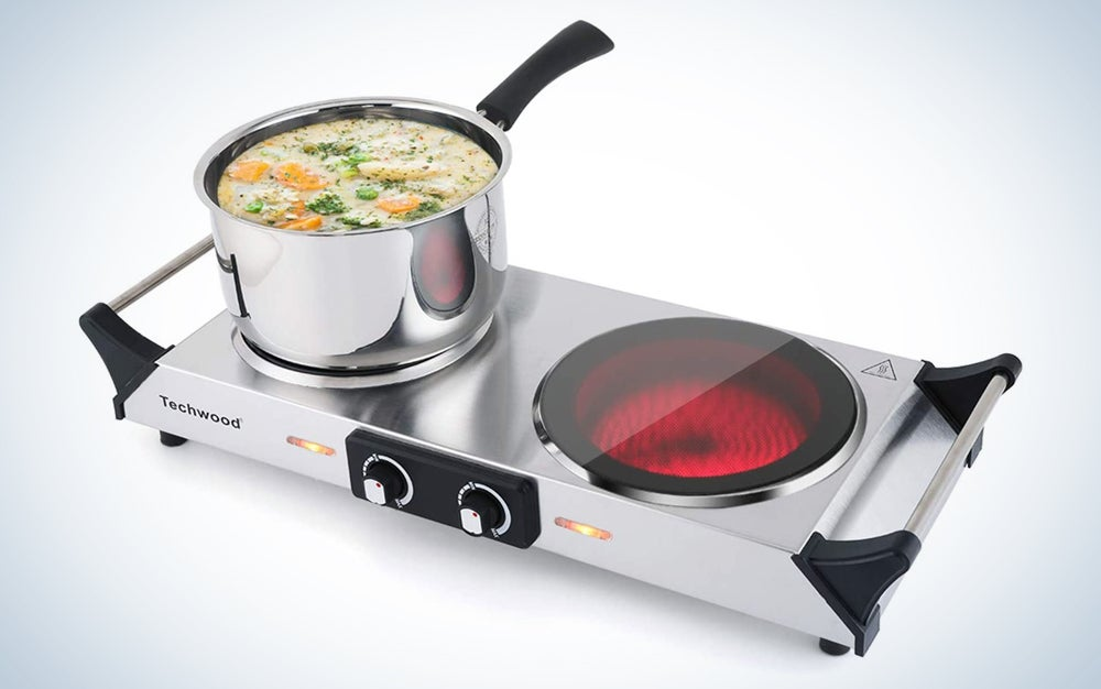 silver hot plate with two knobs on the front, one burner on, and a pot with soup on the other burner