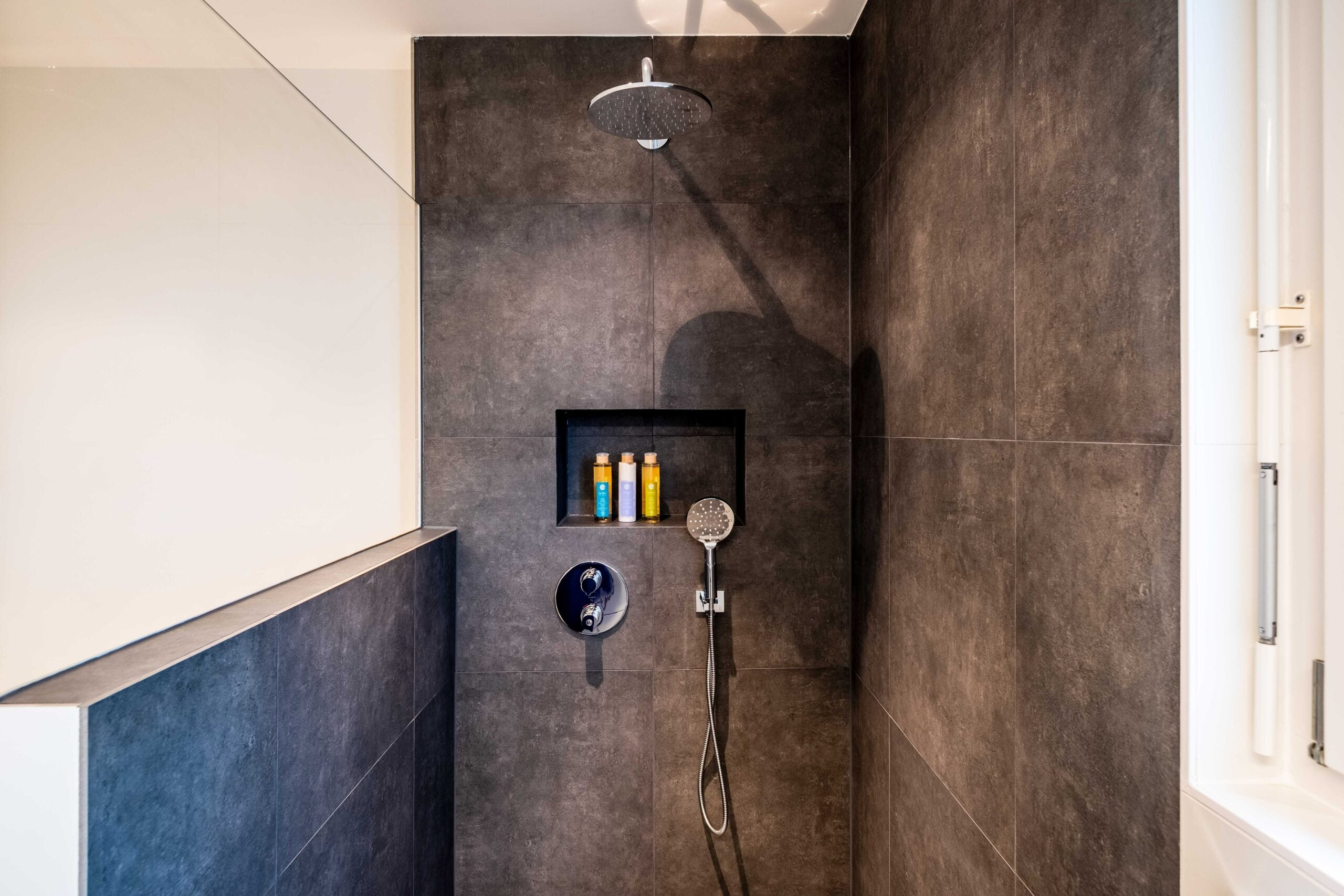 black tile shower with a glass window