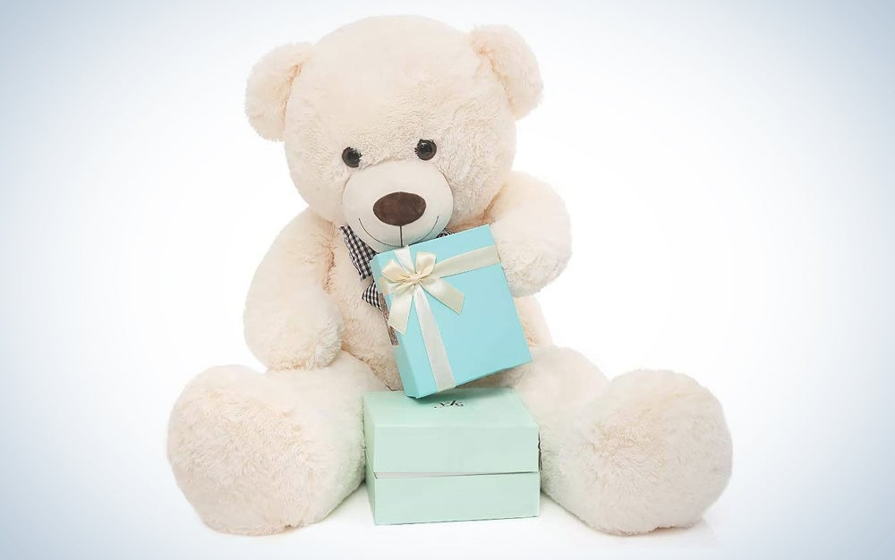 white teddy bear holding two presents