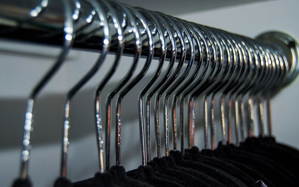 Many grey velvet hangers in line hanging one after the other.