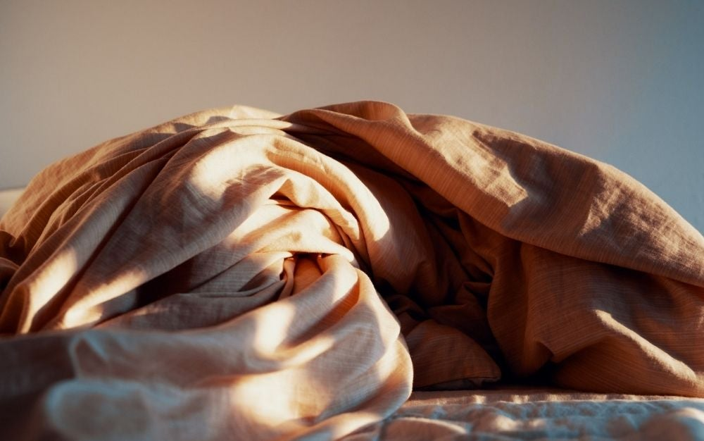 A light brown blanket gathered and with sunlight on it.