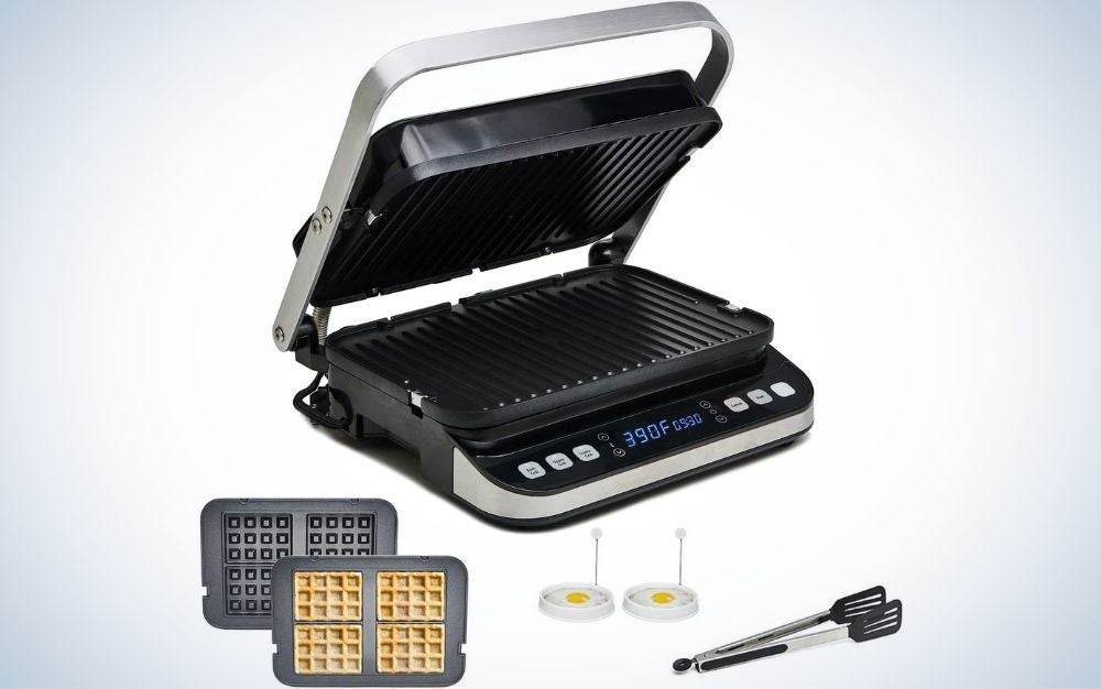 A black panini press with silver lid holder and with other accessories like grill, waffle maker, griddle, and with deluxe accessory kit into it.