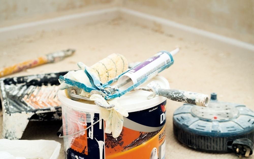 Caulking tool kits, painting bucket, gloves, and a white brush with black stripes