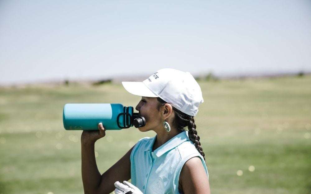 A lady drinking from her celeste motivational water bottle