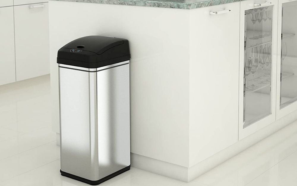 Black and silver vertical touchless trash can standing next to the kitchen