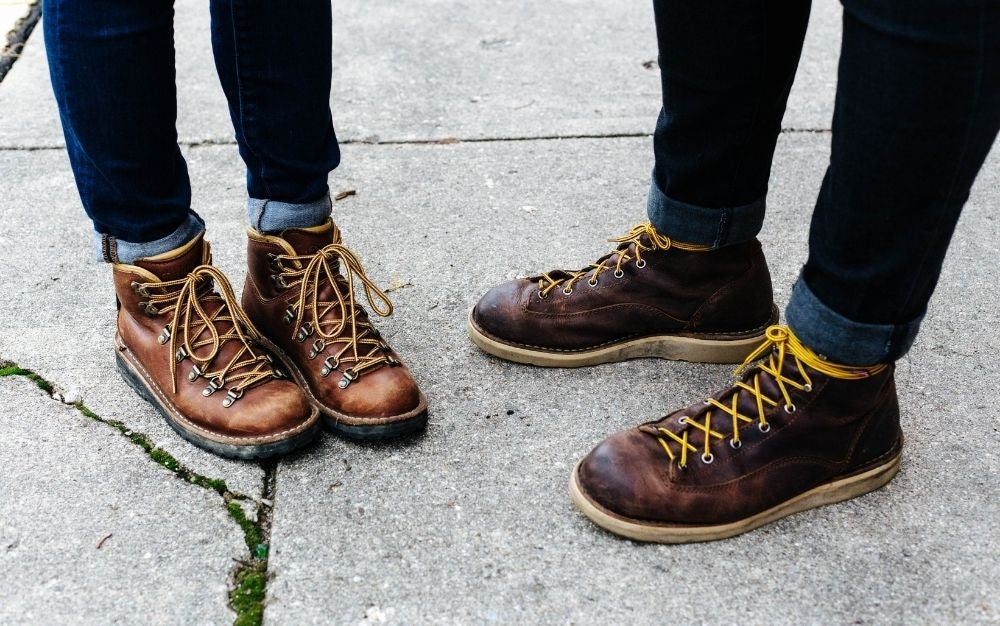 Two people wearing brown shoes with yellow shoelaces