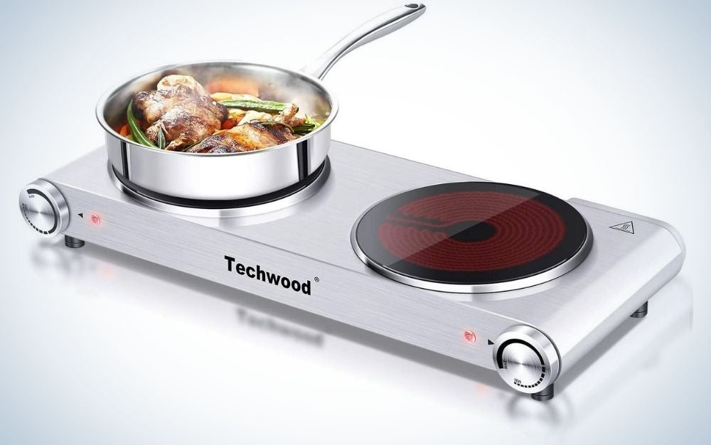 A grey Techwood countertop stove double burner for cooking, with one stove in red color and the other stove with a pan of food in it.