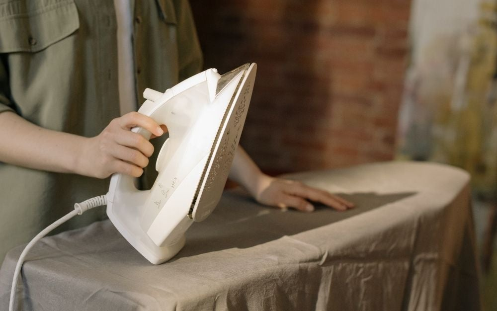 Person ironing a gray sheet with white steam iron