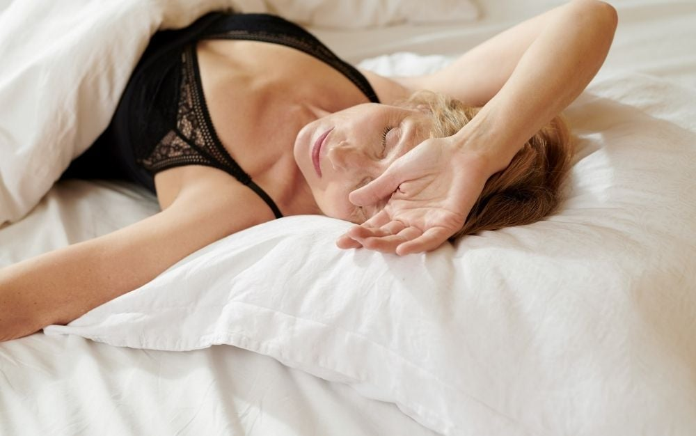 A woman sleeping with her hand on the head and wearing a black shirt, covered with a white blanket.