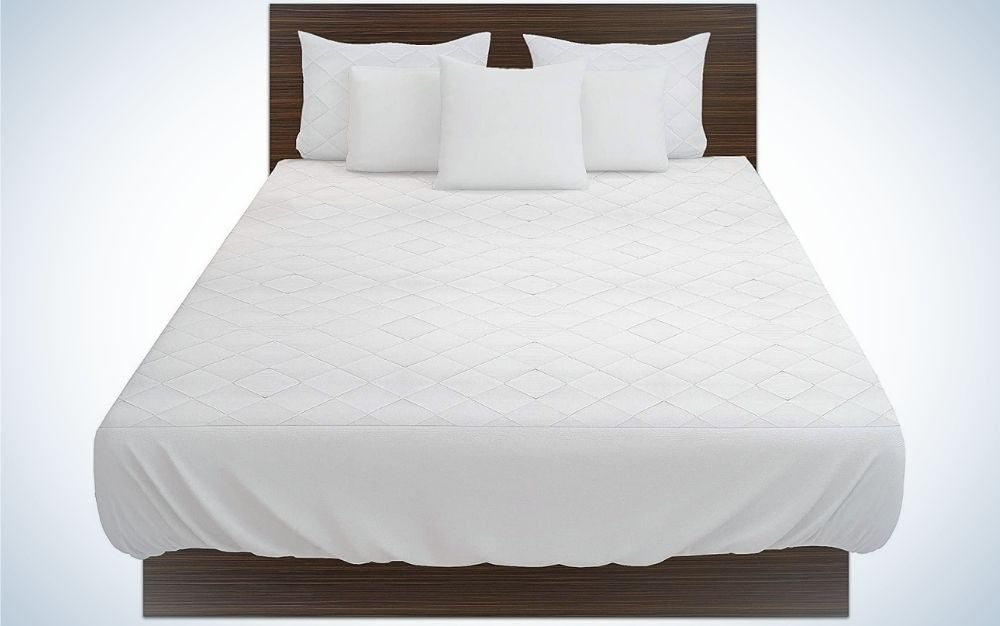 A big double bed with white covers and five pillows in the head of the bed.