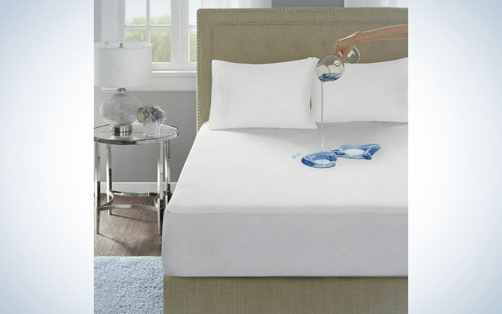 A beige bed with two white pillow and a hand of a woman with a glass with water pouring water on the bed.