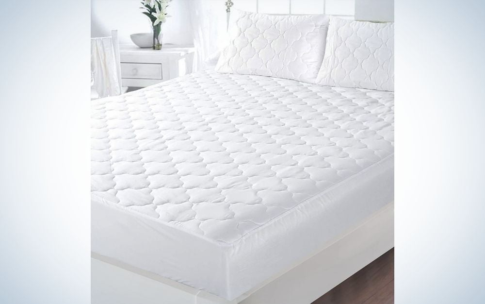 A big room all in white with a bed with a cover all white and two pillows into it.