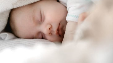 A newborn sleeping in his side with eyes closed.