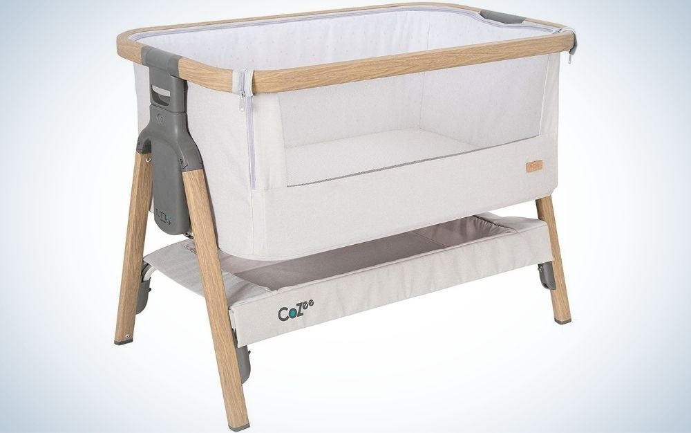 A white bedside crib/co-Sleeper with breathable mesh window and with wooden wheels.