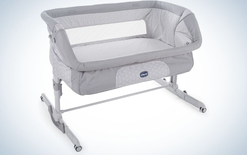 A light grey bedside baby crib with two moveable wheels.