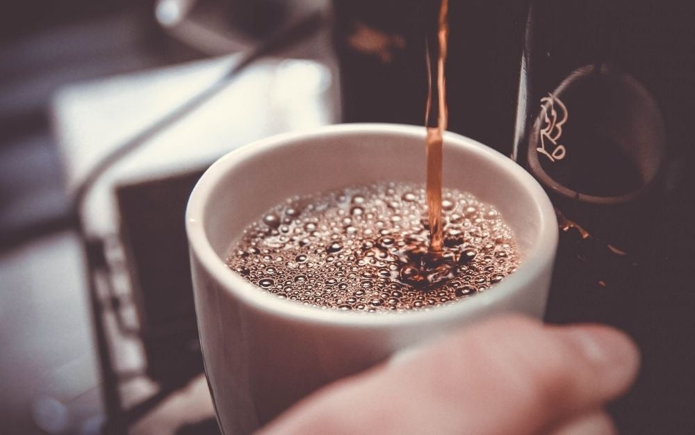 A cup being filled with coffee and being caught by the hand of a person.