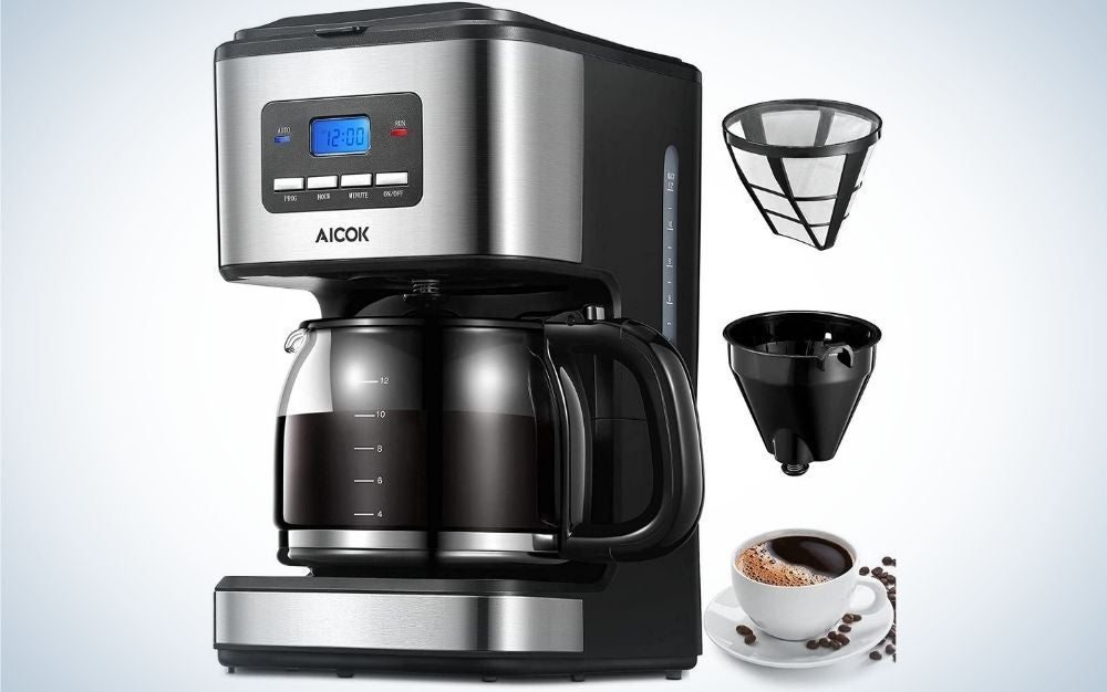 A silver and black coffee maker machine with blue screen with numbers on it and with a pot with coffee into it plus three other items beside coffee maker.