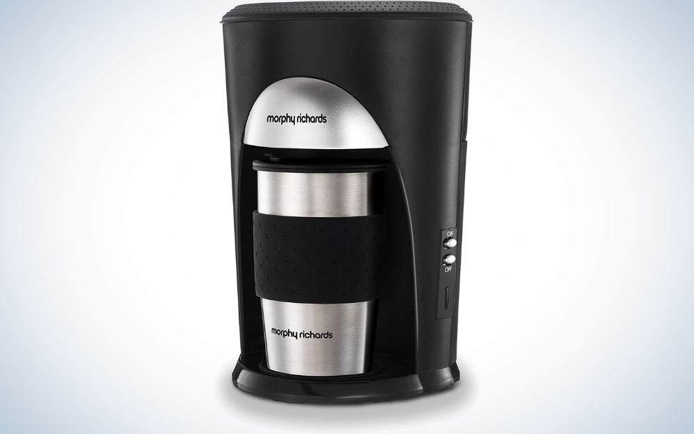 A all black coffee maker machine with an coffee cup inside of it with silver and black color.