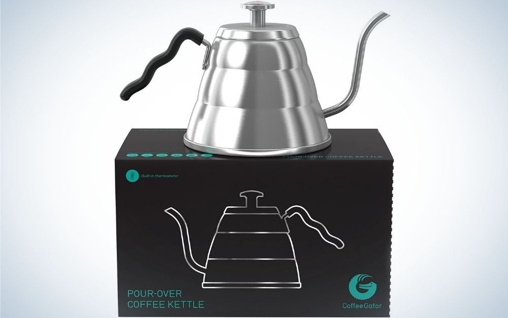 A silver gooseneck kettles with a black holding hand over a black box.