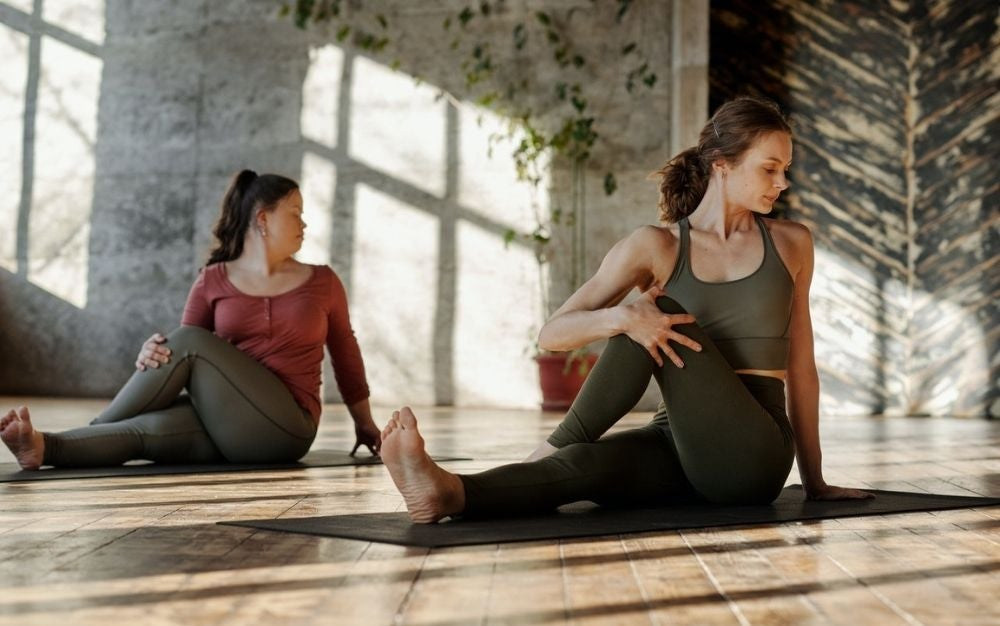 Two young woman wearing yoga clothes and doing yoga into a large room with light and wooden floor.