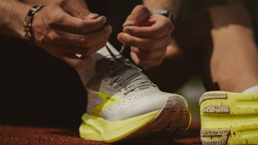 A persons hand wearing a pair of white and yellow athletes and tightening the sneakers.