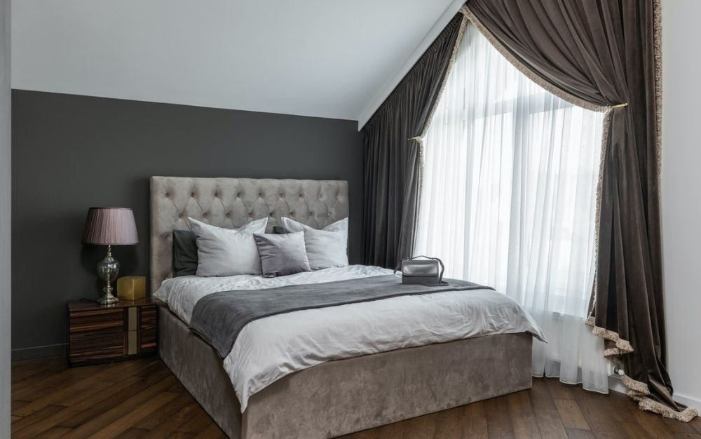 A bedroom designed and interior with grey and white colors, pillows and comforter with a brown wooden floor.