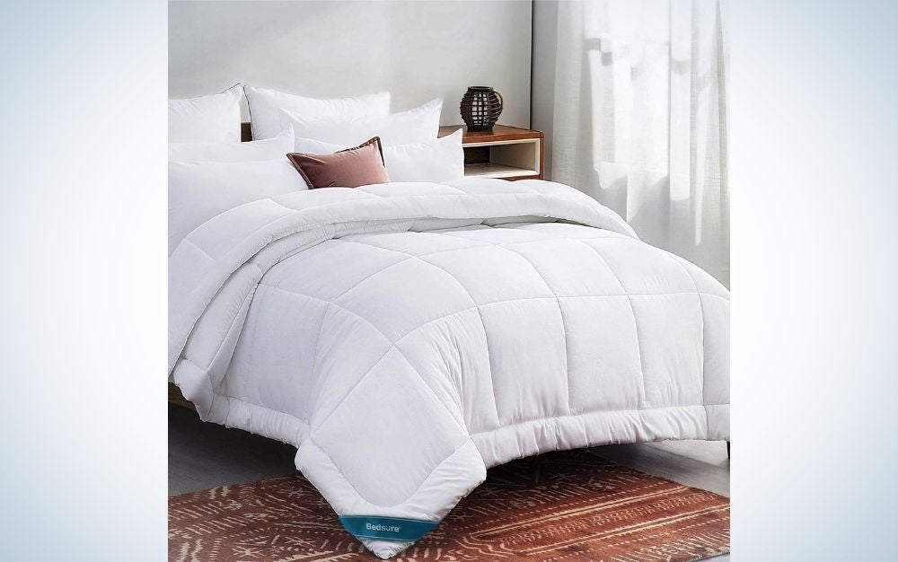 A large double bed with a blanket and lots of white pillows and a small pillow in the middle of brown and with a side bedside table in brown with an ornament on it.