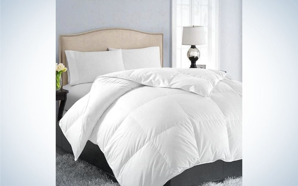 A room with a bed with its beige head with a white cover and pillows as well as a side lamp and flowers on the other side of the bed.
