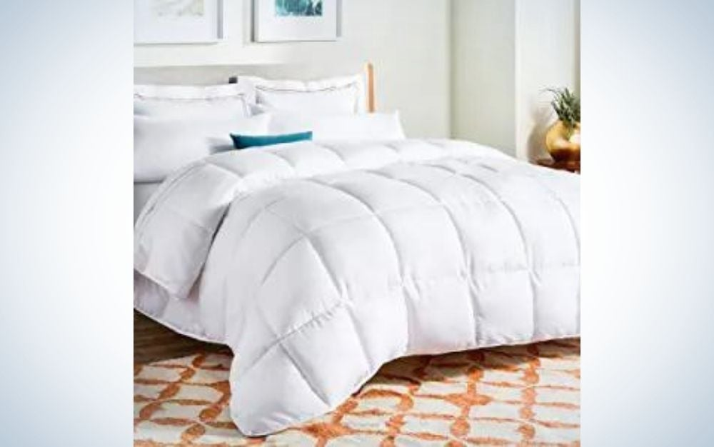 A large double bed with a blanket and lots of white pillows and a small pillow in the middle of green color and with a side bedside table in brown with flower on it and orange and white carpet on the floor.
