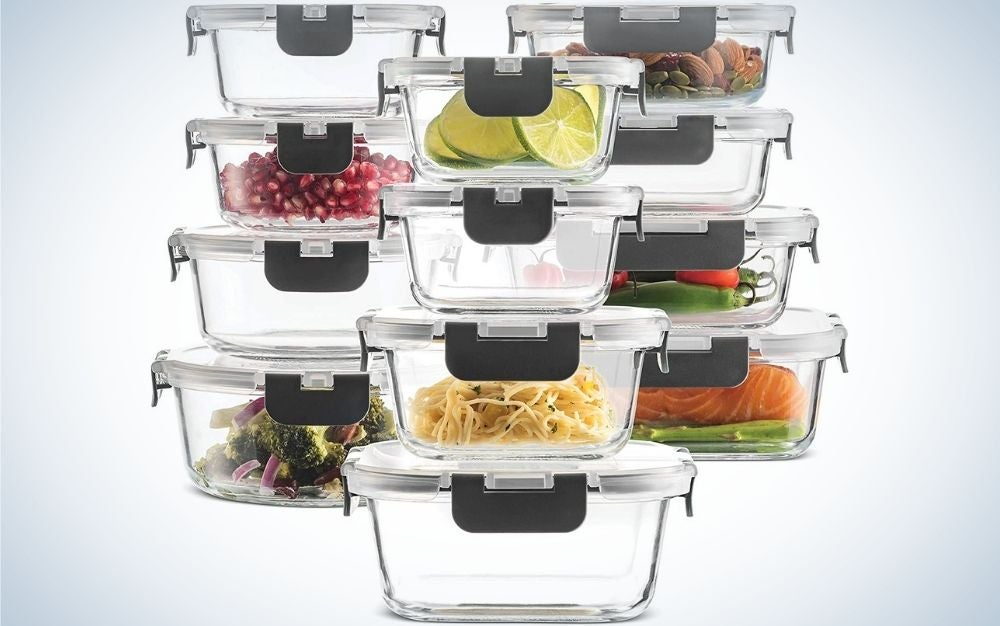 Some transparent glass food containers that stand on top of each other and are filled with food in them.