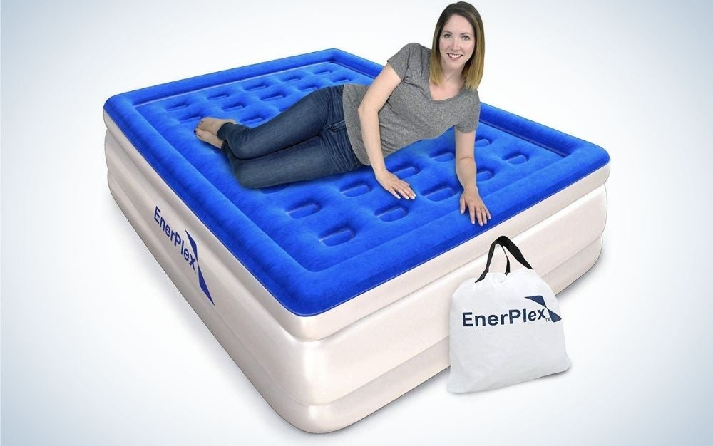 A girl lying down as she looks straight at a large, thick mattress with blue and white air.