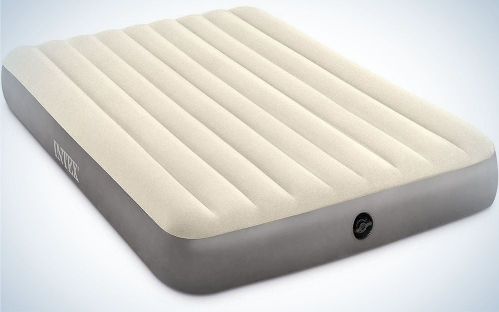 A large and thick air mattress which is dark gray and white gray and above has horizontal stripes on its upper part and on its side there is a large black dot.