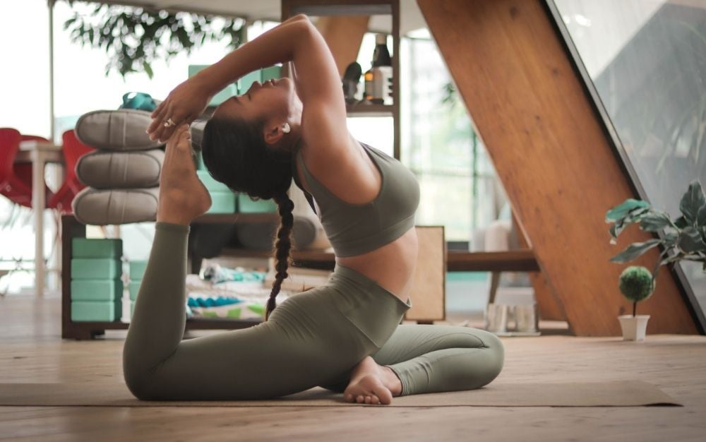 A woman in a room doing yoga and stretching on a wooden floor.