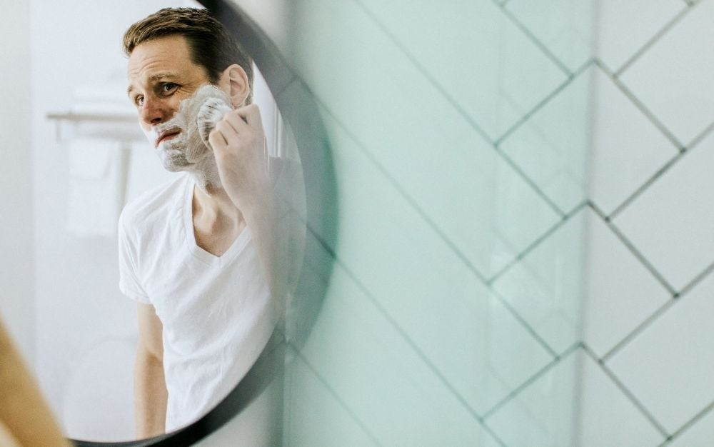 Man shaving in front of a mirror