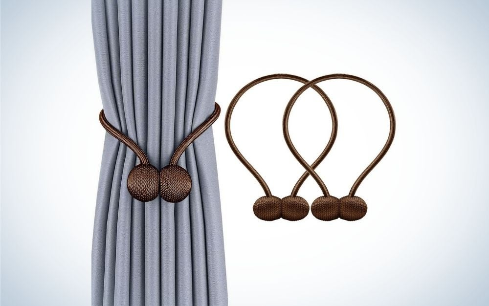 A curtain hanging with a piece of sky blue color and some decorative clips in the shape of a round brown.